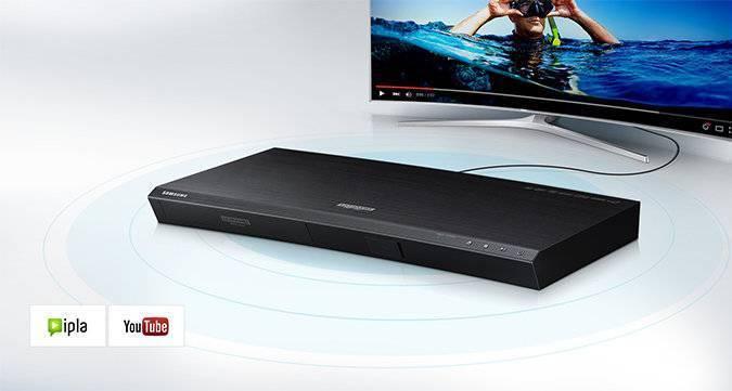 Odtwarzacz UHD Blu-ray K8500 podłączony do telewizora SUHD. W Lewym dolnym roku ikony IPLA i YouTube.